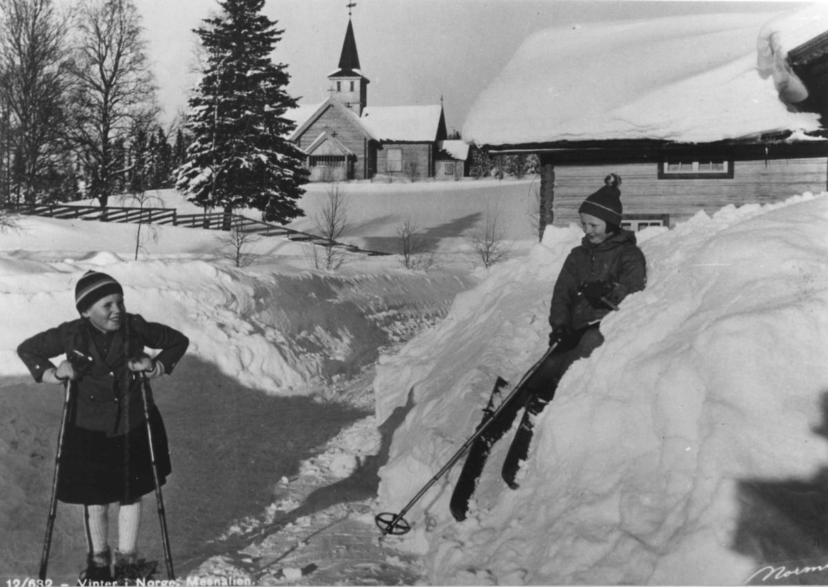 Avfotografert postkort. To barn på ski i vinterlandskap med Mesnalien kirke i bakgrunnen.