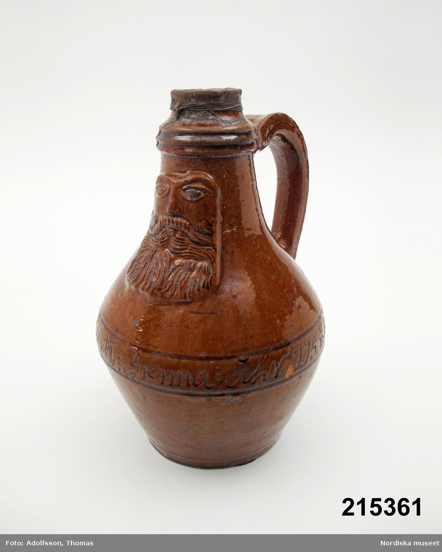 """Krus med ett tyskt """"bartmannskrus"""" av stengods med en skäggig gubbe som förebild. På kruset står: """"Däna Flaskan är giord uti Grenna Åhr 1755 Jacob Sundberg."""" Sundberg var verksam i Gränna 1750-1788. /Annika Tegnér 2005"""