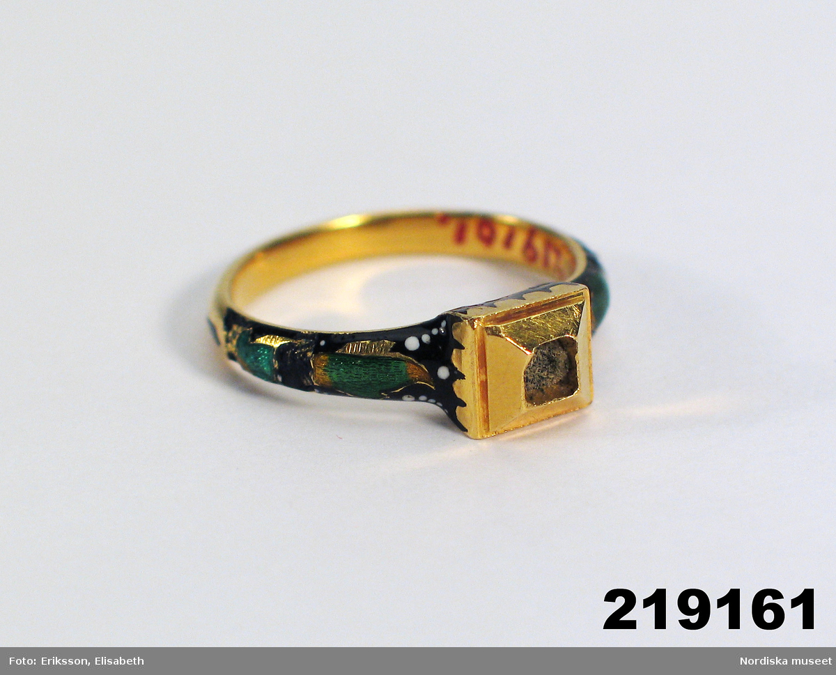 """Huvudliggaren: """"Klackring, guld, emaljerad i färger, stenen i klacken fattas. På insidan av ringen mongogram 'GAB'. Jordfynd från Veinge sn, Halland.""""  Katalogkort """"Ring. Av guld, delvis belagd med grön, gul, svart och vit emalj. Fyrkatikgt framstycke (stenen bortfallen). Inskrift monogrammet GAB."""