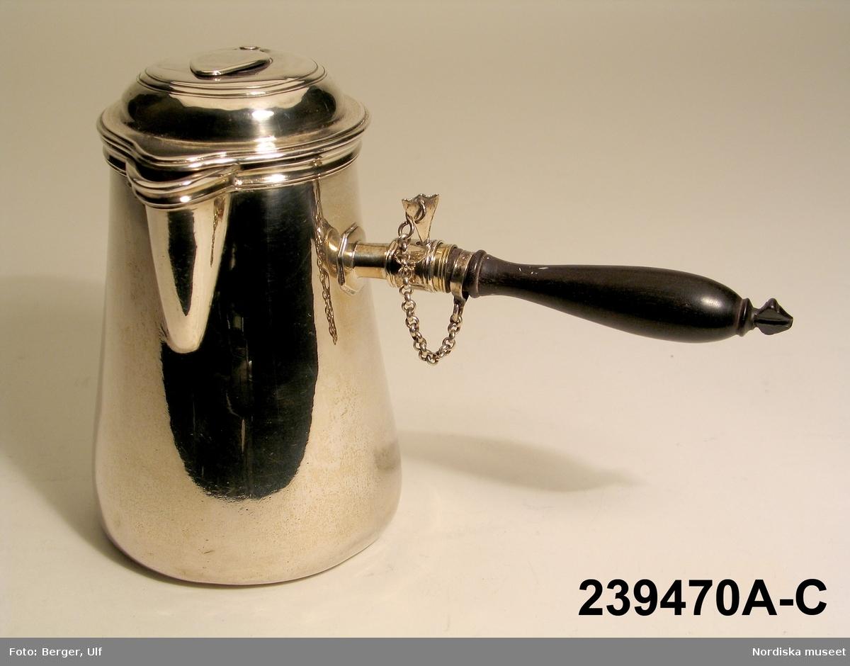 """Huvudliggaren (år 1949): """"239470a-b Chokladkanna, av silver, med fällock som har ventil; svart träskaft, riglad i skruvfattning med vänster-gängning; snås. Gjord 1750 av Petter Friedrich Moldenbauer. Under botten, utom stämplarna, ägarstämpel och åldermansranka samt graverat: 31, 3/4. Förvarad utställd på Tyresö. Skänkt som minne av stadsrådinnan Augusta Ahlströmer, f. Ehrenberg. Gåva 20/12 1949 [av] 1:e Kammarherre, friherre Jean Jaeques De af Finspång. Stockholm."""" a) Kanna. b) Handtag.  Chokladkanna av silver med svart skaft. Grevliga ätten Pipers vapen ingraverat."""
