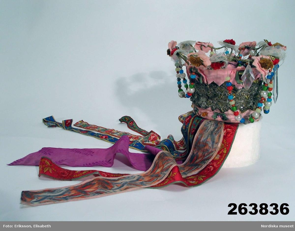 """Katalogkort: """"av konstgjorda blommor, mångfärgade pärlor, glasprismor, skärt, vaxat bomullstyg, knypplade mellanspetsar. Stommen av ståltråd och mässingsbleck. Hängband i nacken av 4 st bomullsband med tryckt mönster, samt 2 sidenband i lila färg med bladmönster, 1 med flamgarnsränder i färger."""""""