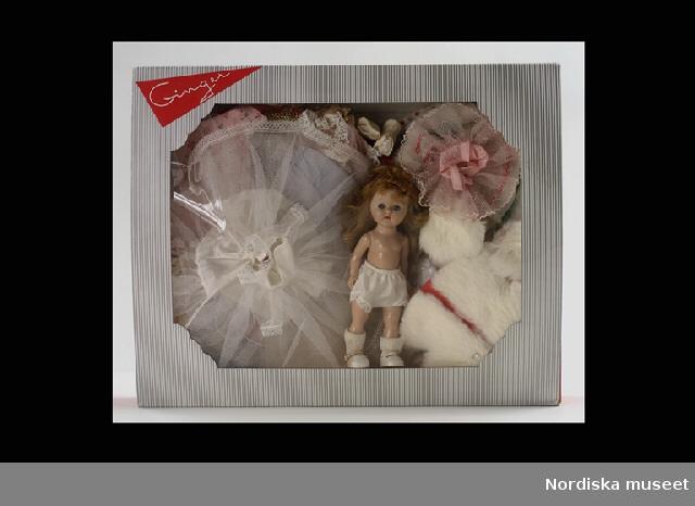 """Inventering Sesam 1996-1999: L 20 cm (Docka), L 41, B 33,5, H 6,5 cm (Kartong) Dockan Ginger, av pressad hårdplast, rörliga ben och armar, blå blundögon av plast, mellanblont långt hår av nylon. Gåmekanism, rör man på huvudet så rör sig benen. Tillverkad i USA av Cosmopolitan Doll & Toy Corp. Klädgarderob inköpt på varuhuset NK i Stockholm, med ensamrätt på försäljningen i Sverige. Dräkterna märkta: """"Fashions for Ginger/Cosmopolitan Doll & Toy Corp./JACKSON HEIGHTS/ TRADE MARK.""""  Kläder av bomull: rutig klänning, tillhörande trosor, blommig klänning, tillhörande trosor, grå-brun klänning, tillhörande trosor och turkos klänning; plysch med pälskant.  Kläder av syntet: ljusblå klänning,vit med röda blommor, tillhörande trosor, rosa nattlinne, rosa neglige, ljusblå långklänning med vitt mönster, tillhörande trosor, rosa långklänning med guldövertyg, tillhörande trosor, slöja guldtyg, rosa skjorta med blommönster, rosa balettkjol, tillhörande trosor, brudutstyrsel med vit balettkjol, trosor, lång jacka/liv och slöja, två vita trosor, ljusblå trosor, ljusblå byxor, sju strumpor, fyra par skor, vita, rosa, gröna och guldfärgade och ett band med blomma.  Kläder av lin: vit klänning med röda dekorationsband.  Kläder av ull: två hattar, en vit och en brun filtad. Kläder av päls: brun mössa med pälskant, vit mössa ett set i vitt med jacka, muff och mössa.  Kläder av plast: regnkappa, tre hattar, en röd med texten """"Fire chief"""", en vit tropikhjälm och en svart med stort brätte, 15 galjar, 6 gula, 4 rosa, 1 röd och 4 ljusblå, fyra par skor, två par röda, ett par bruna och ett par vita, tre väskor, en brun med Ginger skrivet med silverfärg, en röd och förövrigt lik den första och en brun sadelväska på ett rött skärp, brunt skärp, silverfärgade glasögon, rosa spegel, rosa kam, svart pistol, band med paljetter.  Kläder av textilstoff: tre par skor, brun kjol och jacka, skridskor med metall skena och vit sko av textil. Föremål av metall: gevär med snöre i orange.           Kläder av"""