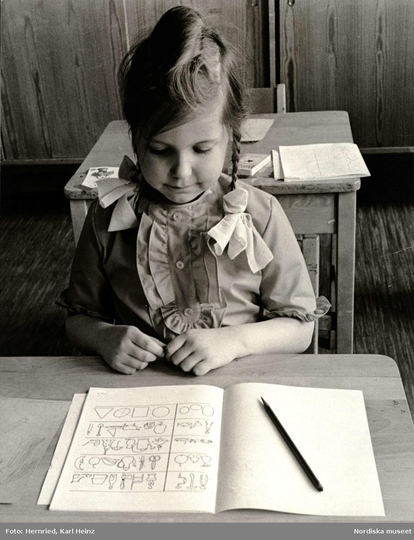 Skolmognadsprov. Flicka i skolbänk av trä med övningsbok och penna framför sig