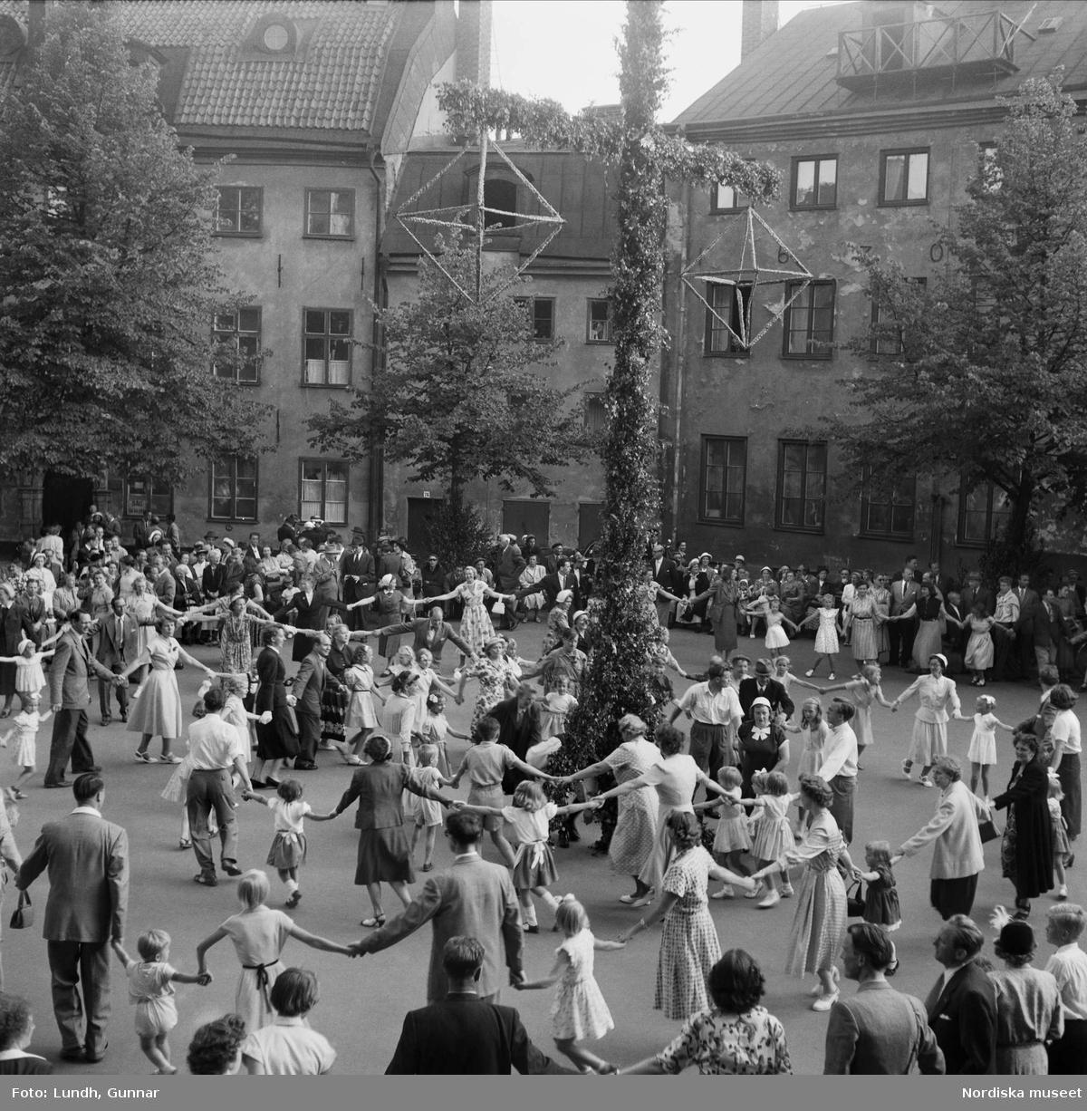 Årshögtider. Midsommar. Midsommar i Gamla stan, Stockholm. Människor dansar runt en midsommarstång på en innergård.