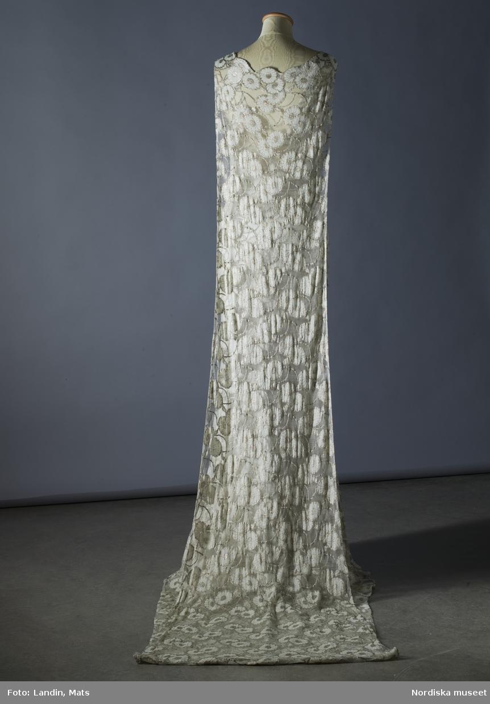 Klänning av ljusgrön peau d'ange med silverblommor. Buren av drottning Astrid av Belgien vid prinsessan Ingrids bröllop i Stockholm 1935. Tillverkad i Paris hos Irène Dana. Nordiska museet inv nr 206293.