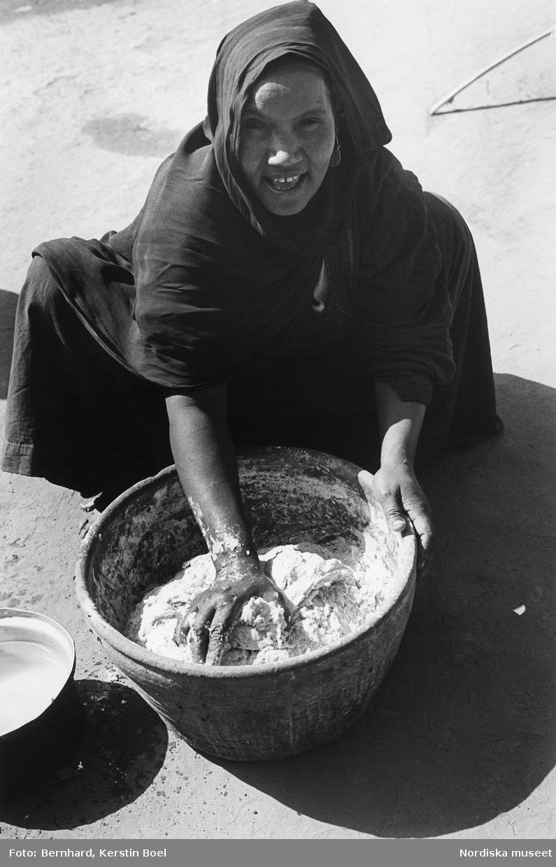 Luxor, Egypten. En kvinna knådar deg i ett lerkärl.