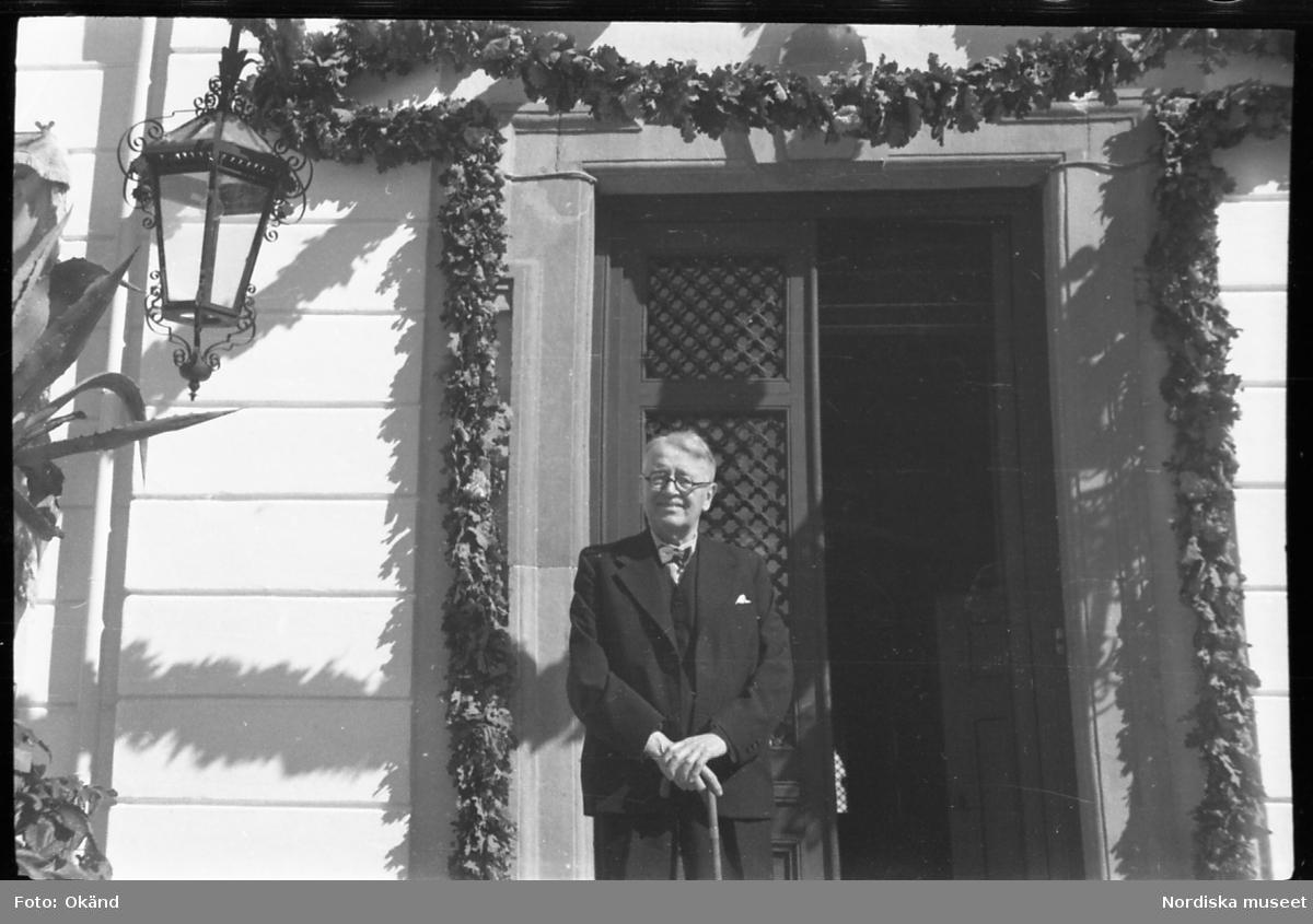 Arthur Bäckström på trappan till Julita gårds huvudbyggnad. Bladgirlang runt dörröppningen.