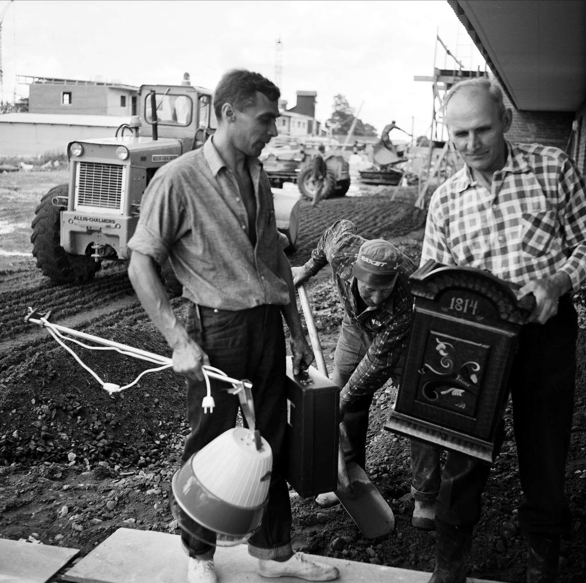 """""""Inflyttning i Bondeparken medan jobbet ännu pågick"""" - Yngve Carlsén och Bo Westberg bär in flyttsaker medan Bror Bohlin schaktar jord, Tierp, Uppland september 1967"""