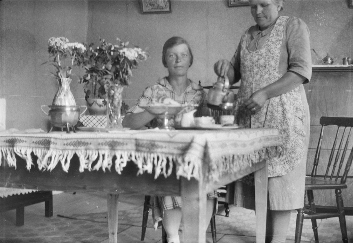 Thea Blom serverar Ebba Spång kaffe i köket på gården Ytterkvarn, Österunda socken, Uppland 1940 - 50-tal