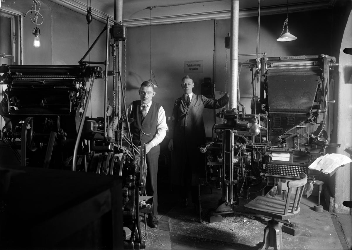 Två män i Upsala Nya Tidnings tryckeri i Oxenstiernska huset vid Riddartorget, Uppsala 1920-tal