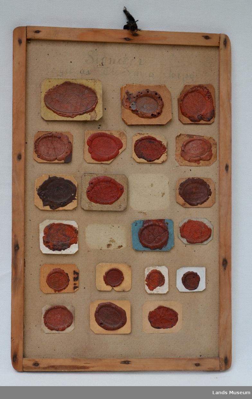 22 stk avtrykk av O.Smeds lakksignetter montert på papplate med treramme.