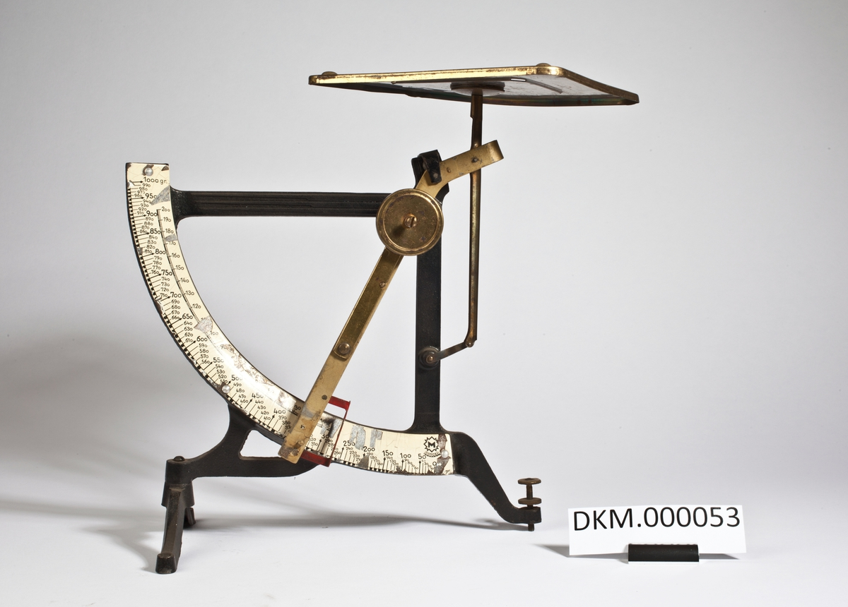 Stativ med en kvadratisk metallplate til å legge de som skal veies på. Den ene foten er regulerbar, og vekta har to skalaer, en fra 0 - 200 gram og en fra 0 til 1000 gram.