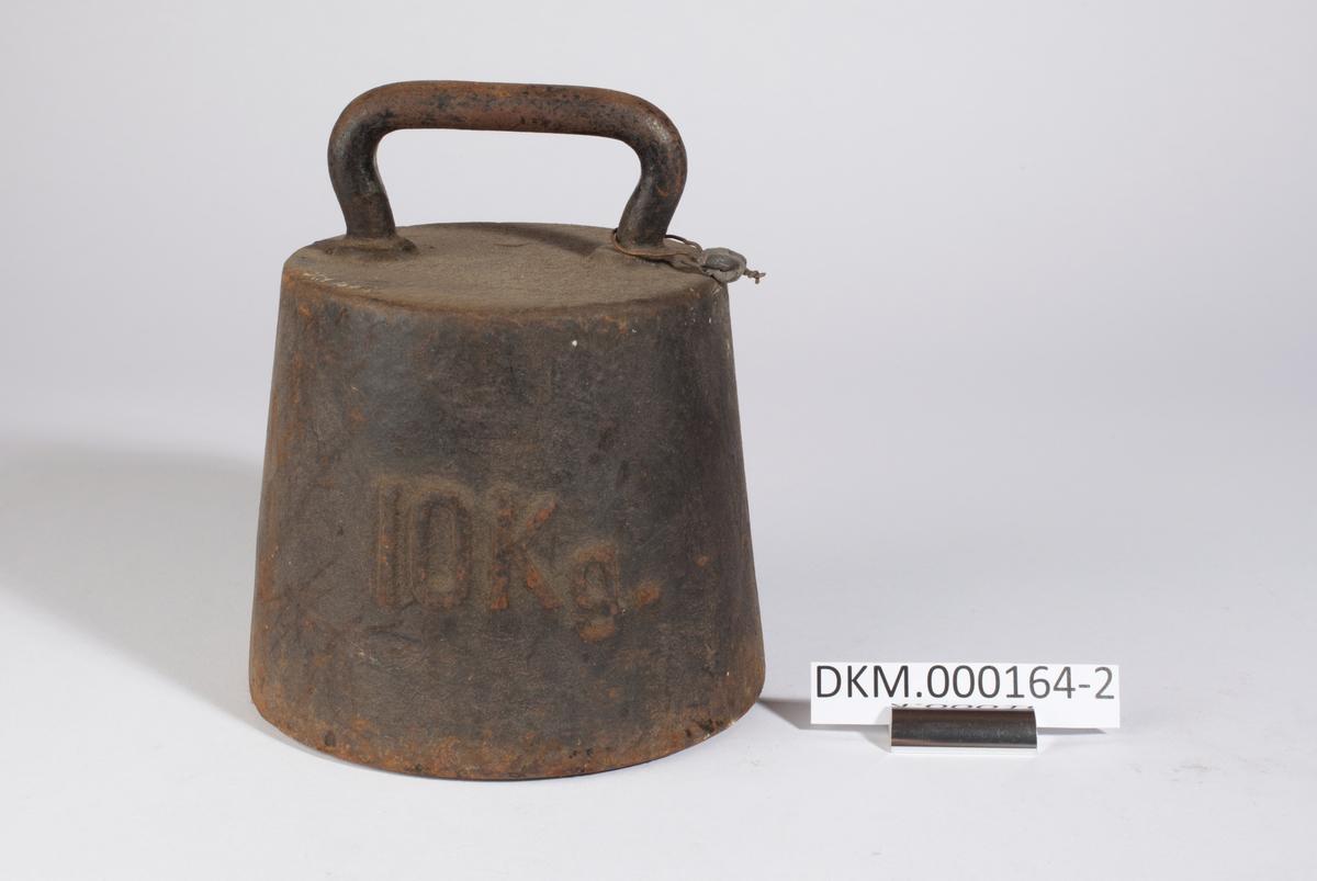 Loddet er formet som en skrå sylinder, det er smalest øverst og har bøylehåndtak. Kontrollstempler i loddet.