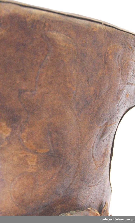 Sydd mønster i skinntrukket sete og bøyle. Trebommen er knekt. Mangler kapper og stigbrett. Skinnet er sprukket i overgangen mellom sete og forsvissel. Messingnagler.