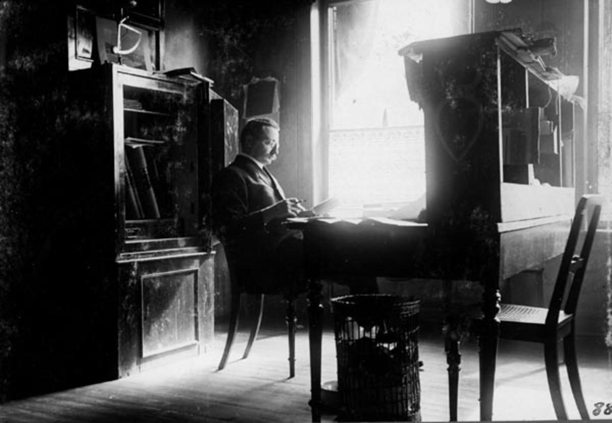 Sekretæren i Christiania Tømmerdirektion [seinere Glomma fellesfløtingsforening], Carl Omsted (1867-1941), fotografert på Tømmerdirektionens hovedkontor i Kongens gate 14 i Kristiania [Oslo].  Omsted var på dette tidspunktet en cirka 40 år gammel mann.  På kontoret var han dresskledd, der han satt på en biedermeierstol foran kontorpulten sin, et langt, rektangulært bord med en hylleseksjon i front.  Arbeidsstedet er plassert slik at det faller lys inn fra et vindu til venstre for sekretæren.  Ved bordenden sto det ei papirkorg.  Bak Omsted ser vi et pengeskap, der døra sto åpen da fotografiet ble tatt.  I skapet skimter vi en del protokoller, antakelig Tømmerdirektionens styre- og regnskapsbøker.  Oppå skapet sto det et stort fotografi fra Glommavassdraget, samt ei brevvekt.  Sekretæren satt og leste i et dokument med et skriveredskap i handa da dette fotografiet ble tatt.   Carl Omsted var sønn av proprietær Arne Arntzen Omsted og kona Marie Antoinette Manthey, som var datter av en høyesterettsadvokat.  Foreldrene eide blant annet gardene Bjerke og Oppaker i Grue i Hedmark.  Arne Omsted skal ha vært en pioner i jordbruket.  Han hadde hatt anledning til å studere gardsdrift både i Frankrike og Skottland, og skal ha innført ayrshirefe, cheviotsauer, yorkshiresvin, turnips og det som seinere ble kalt «ringerikspoteter» i hjembygda.  Han var imidlertid skuffet over hvor liten avkastning jordbruket gav, og han skal ha rådd sønnene sine til å finne seg andre inntektskilder.  To av dem ble likevel framstående gardbrukere i Grue.  Carl flyttet altså til hovedstaden, der han etter endt utdanning fikk den nevnte sekretærstillingen i Christiania Tømmerdirektion, hvor han antakelig fikk glede av den kunnskapen om skogsdrift, tømmeromsetning og skogsdrift oppveksten på en stor skogeiendom i Solør hadde gitt ham, og av den teoretiske kunnskapen han hadde tilegnet seg i byen.  Carl Omsted giftet seg med Anna Marie Mürer, som var oppvokst i en grossererfamilie i Kargerø. Carl fikk
