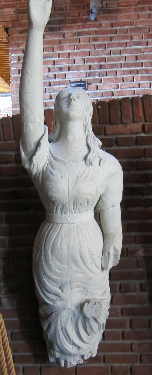 Kvinnefigur med høyre arm hevet, venstre underarm mangler.