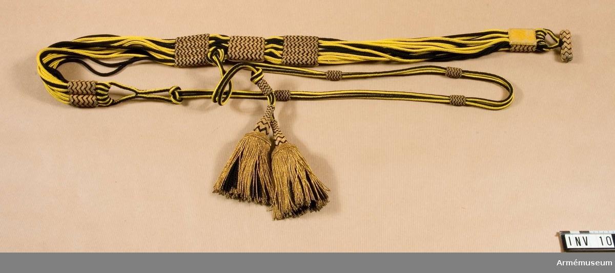 Bäres till dolma m/1895. Består av gula och svarta silkesnören sammanhållna av guldknutar. 2 baktill och 3 framtill. Vidhängande gulsvarta silkesnören med två tofsar i guldtråd och svarta silkesnören. Har tillhört Gustav VI Adolf (1882-1973).