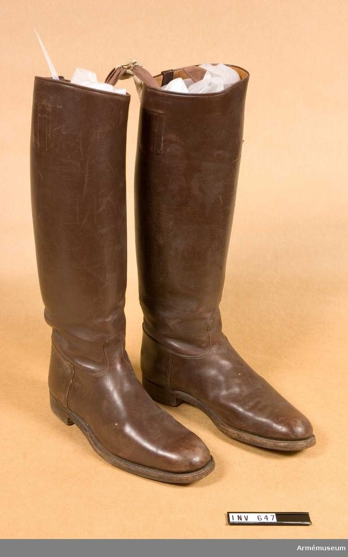 """Stövlar av sk tillåten modell. Stl 4. Höger och vänster stövel, bruna med låg klack och  tämligen rund tå. Själva skon har sömmar på in- och utsidan av  foten. Över vristen går det upp en liten plös, faststickad med  dubbel söm. Randsyddsula. Skaftet förstärkt i sömmen mitt bak med en remsa av läder, samma som för stöveln i övrigt. 17 mm  bred. Stöveln är helfodrad med något ljusare läder. Har två  dragtampar av brunt kypertband inne i skaftet. En på var sida om benet. Vänster stövel märkt framtill inne i skaftet: """"MEA  Stockholm"""". Inne i skaftet på vänster sida står """"44  428  9"""". Höger stövel märkt inne i skaftet högersida: """"44  428  9"""". Båda märkta under hålfoten """"4""""."""
