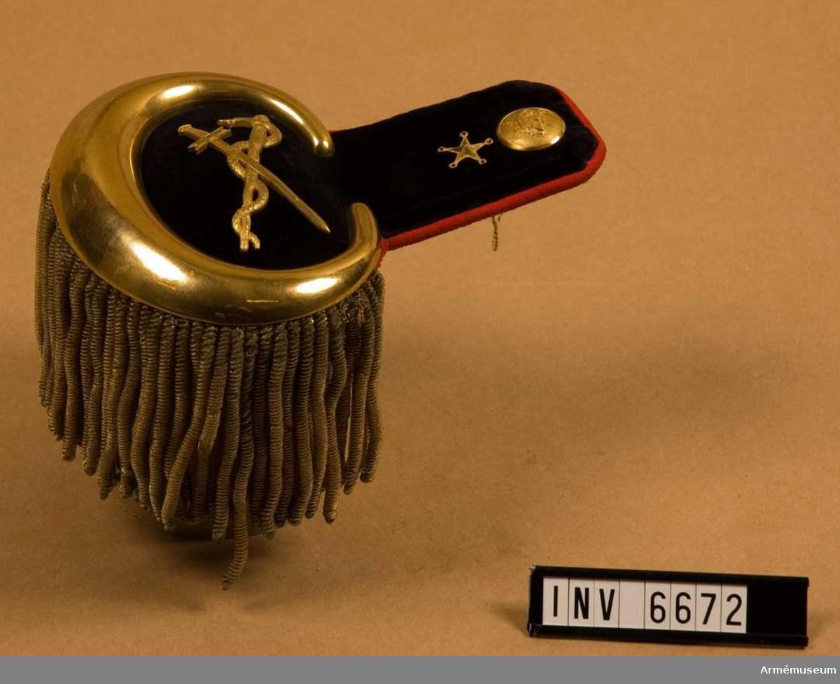 Gott skick. Mått: 190 mm mittlängd, 125 mm högsta bredd. Epålett med matta av svart sammet och med foder av rött kläde. Omkring Övre delen en röd passpoal (fodret) samt omkring nedre  delen en förgylld plåt. Ovanpå nedre delen av mattan en  förgylld esculapiistav och ett förgyllt svärd, korsande varandra. Knappen m/1817 av fältläkarkårens modell och en  förgylld stjärna som gradbeteckning. Epåletten är försedd med buljoner i guld. Epåletthaken är märkt: Morell & CU.Regementsläkarna, en vid varje regemente, hade majors rang. De  skulle ansvara för hälso- och sjukvården därstädes.
