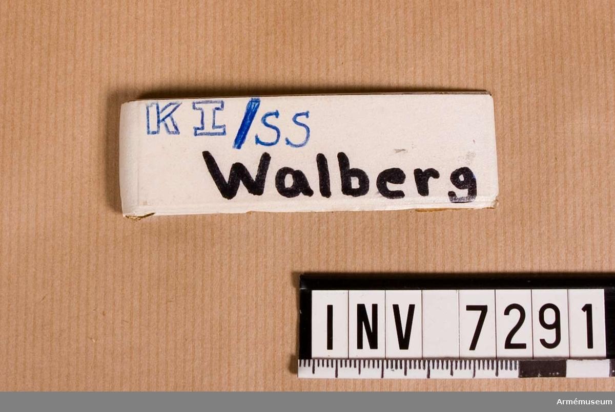Utförd i aluminium med klämma. På framsidan påsatt en remsa av vit tape. På tapen är skrivet med svart spritpenna: Walberg. Däröver är textat med bläck: KI/SS.