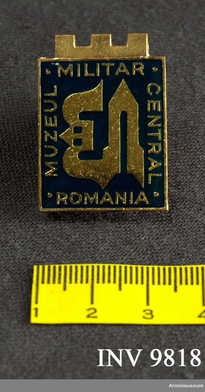 Märke från Muzeul Militar Central Romania. Ett metaIlmärke som kan fästas på plagget med en nålhake. Framsidan är i blå emalj med en stiliserad dekor i guld med omskrift i guld enligt följande:MUZEUL MILITAR CENTRAL ROMANIA. Märket förvaras i plakettasken.