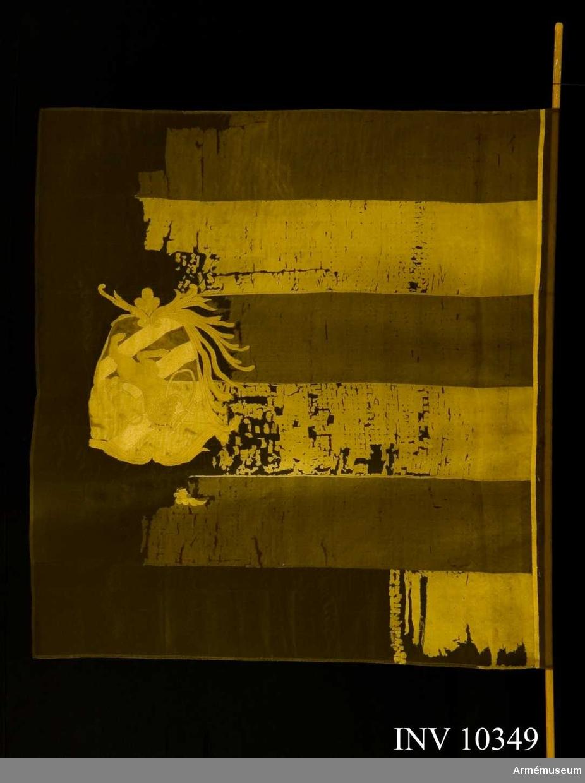 """Grupp B I.  Duk av sidenkypert, fem gånger delad i gult och svart. I mitten broderat Göteborgs vapen på blått fält med tre vita strömmar snett från vänster varöver ett framåtvänt krönt lejon i gult silke förande ett svärd och en sköld vari """"tre kronor"""" på blått  fält allt i en av stiliserade palmkvistar i gult silke bildad sköld, krönt med öppen krona i gult silke med rött foder samt  pärlor i silver, kantad med gult sidenband, fäst med liknande sidenband och förgyllda spikar. Höjd 151 cm, bredd 106,5 cm. Spets, holk och doppsko saknas."""