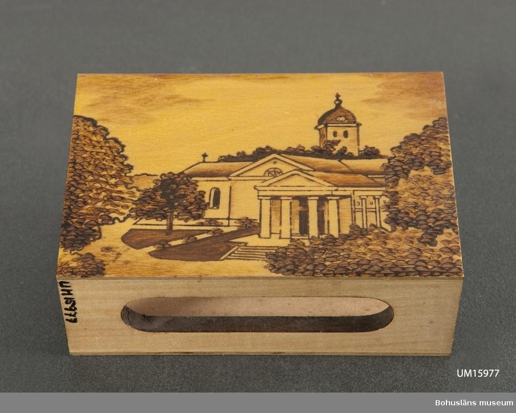 """Öppningar för plånen i sidorna. Framsidan pryds av bild över Uddevalla kyrka, gravkapell och klocktorn. På baksidan namnet """"Uddevalla"""" glödritat.  Se UM015810"""