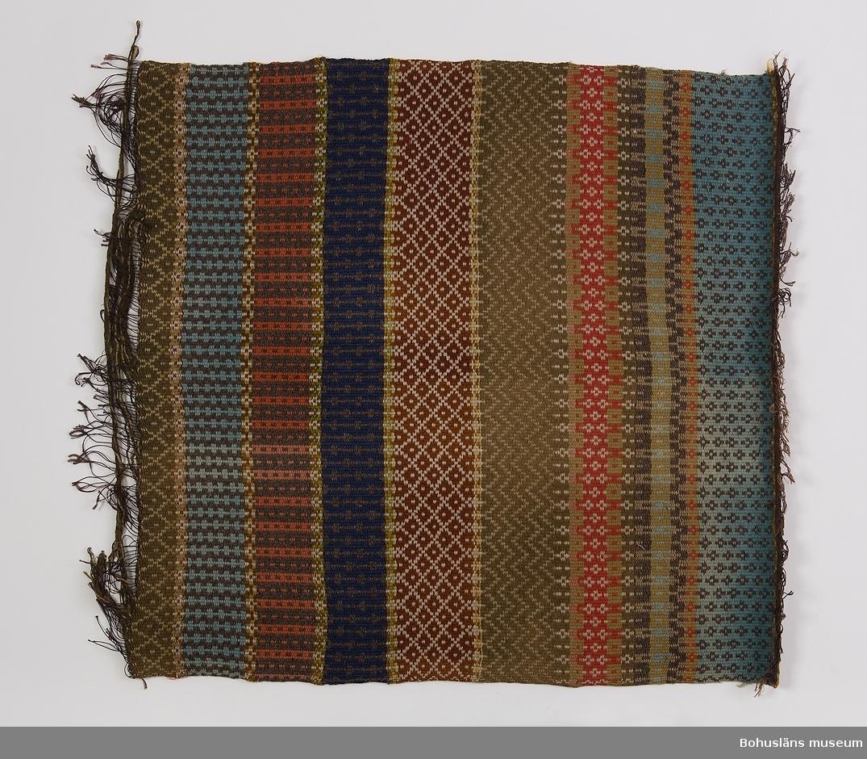 Vävnad i bunden rosengång, solvad på 4 skaft. Helt mönstrad, med mönster i bårder med stapelmönster, H-mönster, rombmönster och sicksackmönster mm. Mörkgrått melerat är kombinerat med gröntonat ljust blått (turkos), mörkblått eller bruntonat rödgult. I andra bårder överväger brunt eller ljust och mörkt gröngult. Litet vitt och stänk av ljusgrönt och gult ingår också. Inslagen är gjorda med ullgarn.  Varpen är av mycket mörkt blå bomullsmattvarp. Varptrådarna är sammanknutna  fyra och fyra i ena sidan. I boken Hemslöjd (Nylén 1978) finns en detaljbild av mönstret på ett Bohusländskt täcke vävt på 1880-talet vars mönster delvis överensstämmer med mönster på denna vävnad.   Med dateringen till 1900 ca menas inte att vävnaden med säkerhet är gjord 1890-1910 utan att den kan vara från slutet av 1800-talet men lika troligt från första delen av 1900-talet.  Mycket trasig i ena kortsidan, väven på väg att gå upp. Delvis blekt.  För ytterligare uppgifter om givaren se UM016001.