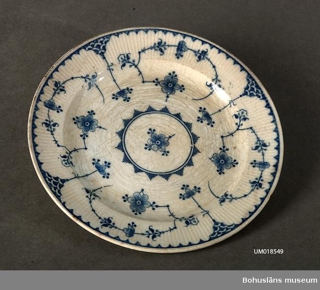 """594 Landskap BOHUSLÄN 503 Kön MAN 394 Landskap UPPLAND  På undersidan märkt: """"Gustavsberg"""" och """"ALVA"""" i blått tryck. Målad blå dekor med stiliserade blommor. Krackelerad.  Se UM18527."""