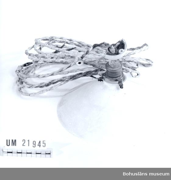 594 Landskap BOHUSLÄN  Lamphållaren som skall fästas i taket är sönder. Ledningen är tvinnad och vit målad. Den vita kupan sitter fast med tre mässing skruvar.  UMFF 66:7.
