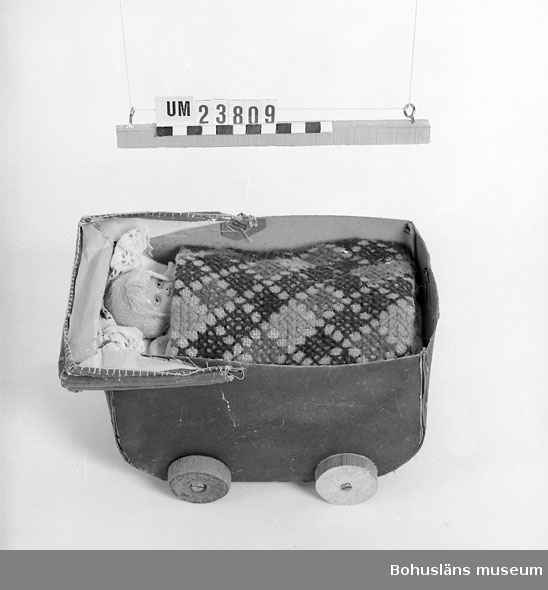 Dockvagn av papp hopsydd samt limmad på botten av trä, sufflett av vaxat papper med bågar av järntråd. Utsidan i blått, insidan naturfärgad.  Docka av konstharts L16, 5; B8,5 cm. Klädd i beige mössa, vit klänning med ljusbruna  prickar, strumpor och sockor i beige. Sängkläder består av: 1 st madrass, vit med ljusbruna ränder, 1 st underkakan, 2 st kuddar ena gul andra röd, 1 st örngott i vitt med  spets, 1 st överlakan med broderad spets, 1 st spetsbit i brunt, 1 st lapptäcke med fyrkantiga bitar på undersidan på översidan rutigt i  korsstygn på säckväv i rött, grönt och blått, st stickat täcke i gul  bomullssatin med vit baksida, 1 st överkast? vitt, maskinstickat, virkat spetsliknande mönster i ändarna.  Snarlik med UM023808.  Personuppgifter se UM023791. Se även UM023804.  UM154:12, 155:1.