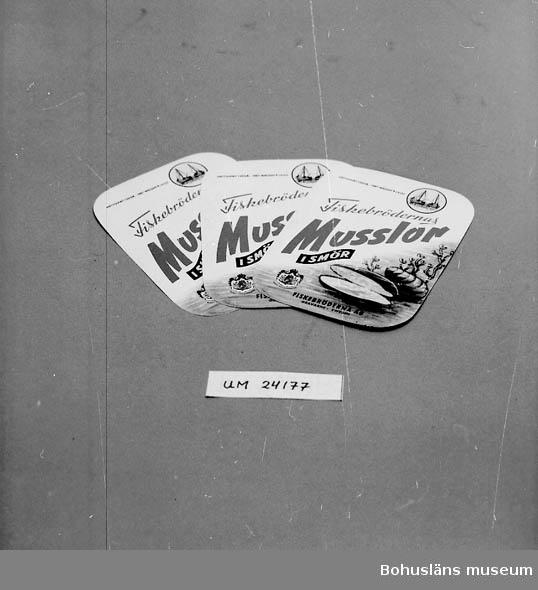 """594 Landskap BOHUSLÄN  Text på etiketten: """"NETTOVIKT 120 GR. NET WEIGHT 4 1/4 OZ. Fiskebrödernas Musslor i smör, FISKEBRÖDERNA AB, GRAVARNE, SWEDEN"""". Bild på musslor. Fyrkantig etikett med rundade hörn."""