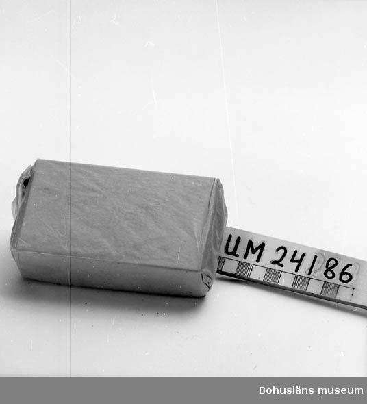 """151 Sakord *, INSLAGET Presentförpackning. Tändsticksask (Tre Stjärnor, Säkerhetständstickor) ligger i ett specialtillverkat fodral av stål med svart tryckt text. Fodralets undersida har fyra runda fötter. Tändsticksasken + fodral ligger inslaget i ett brunt silkepapper förslutet med en bit av företaget Luckey konservfabriks pappersklisterremsa. Text på fodralets framsida: """"Stormen"""" Ansjovis, """"Brottsjö"""" Sill"""". Text på en långsida: """"Kvalitetskonserver. Etablerade 1893, 50-årig erfarenhet till konsumenternas tjänst"""". Text på undersidan: """"Tillverkningar: ANSJOVIS Specialitet: """"Stormen"""" Marknadens förnämsta. Alla sorters hel och skinn- & benfri ansjovis. GAFFELBITAR Specialitet: """"Brottsjö"""" Sill och """"Luckeys Utvalda"""" RÖKTA INLÄGGNINGAR I OLJA Specialitet: Rökt Makrill i tunna skivor i olja. Sardiner och Herring. KAVIAR, FISKBULLAR m.m. A.-B. ELIS LUCKEYS KONSERVFABRIK, LYSEKIL. Tel. Namnanrop """"Luckeys"""".  Övrigt material från AB Elis Luckey: UM15081:1-41, UM17232 - UM17394, UM18076-UM18120, UM24155-UM24156, UM24186-UM24188 samt UM31292 - UM31293.  Materialet utgör en samlad gåva från Cai Luckey, Lysekil, sonson till grundaren av företaget, AB Elis Luckey.  För uppgifter om företaget och övrigt material från Luckeys konservfabrik i samlingarna, se UM17232."""