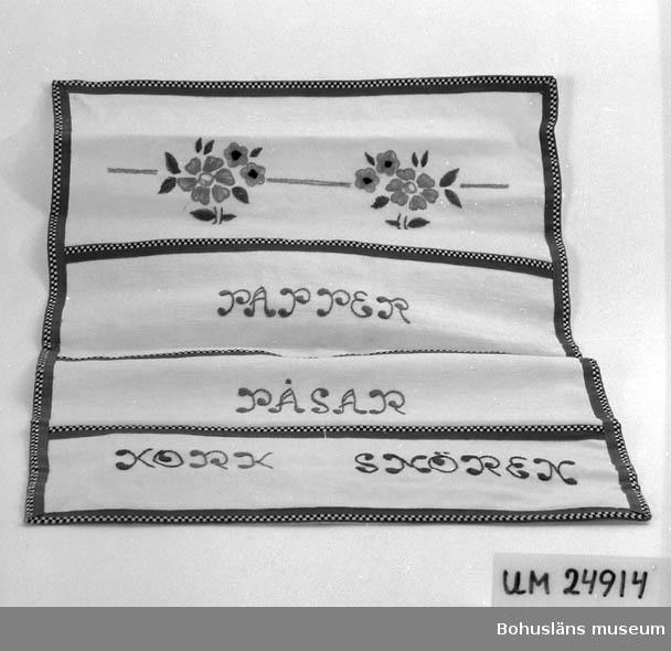 """Vitt tyg kantat med blått och svart och vitt rutigt bomullsband. Fyra fickor.  På fickorna är det broderat i blått: """"PAPPER PÅSAR KORK SNÖREN. Broderade blommor högst upp, färg: Rosa, grönt, blått och svart. För upplysningar om ägarna, Gunnar och Greta Karlsson, se UM018527. Gåvan omfattar UM024884 - UM024915"""