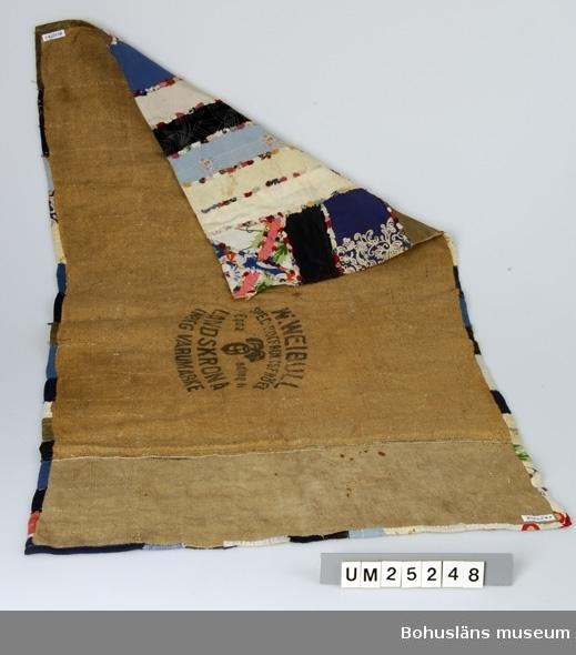"""Emilia Larsson, född i Tossene. Pappan finstenhuggare i Hunnebostrand. Gift och bosatt på gården Ellene mellan Tossene och Hunnebostrand.  Familjen flyttade till Ellene gård när Elsa (1918-2003) var liten. Mellan 1920-1925 beställdes mattan av en granne, en äldre dam """"Charlotte i Svenseröd"""". På undersidan av grov säckväv i jute finns stämpeln """"W. Weibull, spec rotfruktsfröer. Egna odlingar. Landskrona. Inreg. varumärke"""" tillsammans med bild av en rova. På framsidan lapptäcksmönster av bitar av bomullstyg, konstfiber samt stickat mönster, trol. från en tröja. Bitarna fastsydda i mönster, i mitten liksidigt kors i rektangel och däromkring tygbitar i olika former. Mellan alla tyger bårder av små tygfragment i olika färger.  Litteratur: Kerstin Ankert/Ingrid Frankow, Den svenska trasmattan, en kulturhistoria, Prisma 2003."""