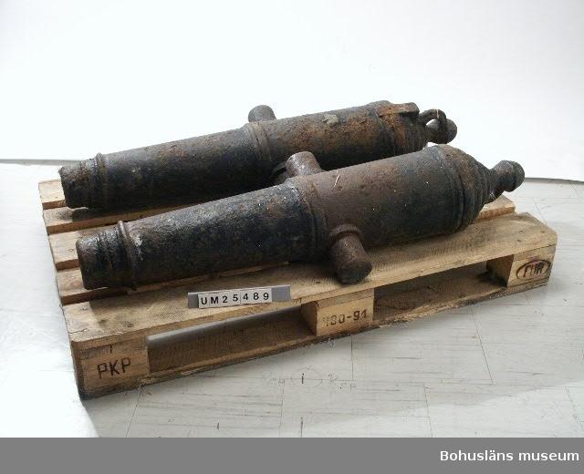 Två kanonrör i gjutjärn till kanoner. På bakre delen finns en ingjuten kunglig krona i relief. På sidorna cylindriska tappar som fungerar som lavettstöd.