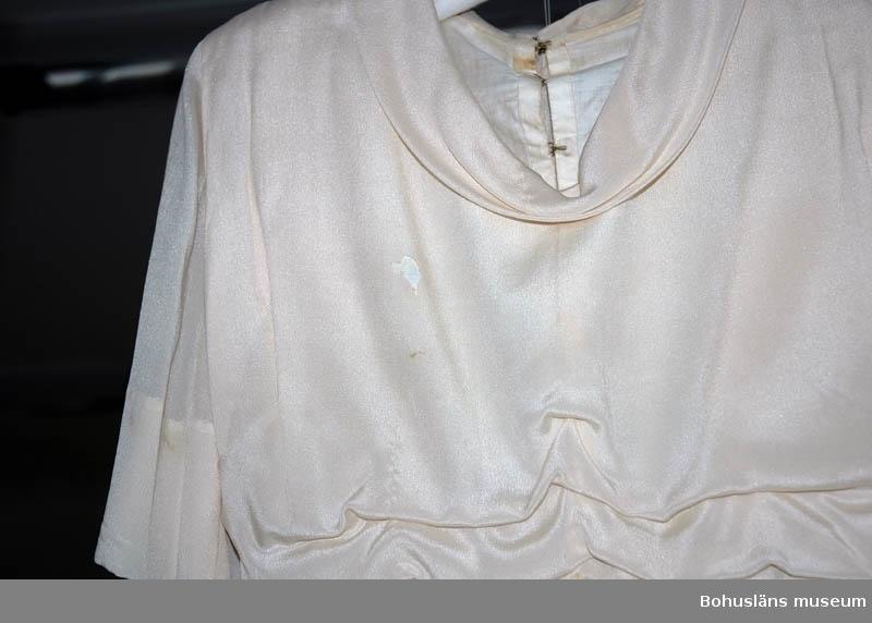 Champagnefärgad (med dragning åt svagt lila/rosa) brudklänning i crepe de chine. En överkjol kortare framtill och undre kjol av ankellängd. Mellan kjolarna på framsidan infällt spetsparti. Lätt veckad kjol. Löst hängande liv med tre lösa veck nedtill. I sidorna infästade skärp i samma tyg att kunna knyta ryschen. Avslutas med en tofs. Livets rygg knäpps med små klädda knappar. Bristningar i tyget.  Sammanhör med brudnäsduk UM025907  Desideria Strandberg verksam som sömmerska med egen ateljé i Lysekil i alla fall från år 1899.  Tillbehör till bruddräkt se UM025743 - UM025746. Gåva av brukarens son. Personuppgifter se UM025730 och UM025739.