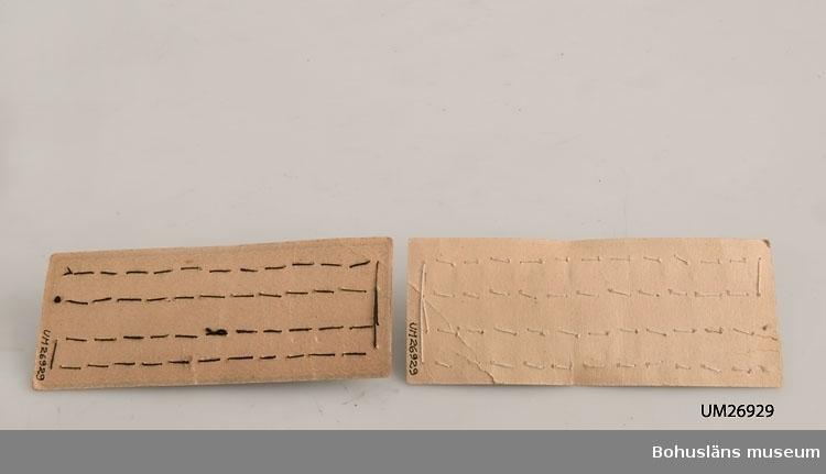 """Två kartor med hakar och hyskor av metall fastsydda (för hand?) på bitar av tjockt papper; oanvända. 24 hakar och hyskor på varje papper (två dussin), fastsydda i rader med 12 längs med papprets långsidor. På pappret finns tryckta mönsterbårder, text mm i blått. På den ena kartan svarta hakar och hyskor fastsydda med svart tråd och tryckt på pappret: """"No 3 GUSUM"""" samt Gusums bruks fabriksmärke, en svan och texten """"FABRIKS-MÄRKE"""" i en rombformad ram. På den andra kartan silverfärgade hakar och hyskor fastsydda med vit tråd och tryckt på pappret """"No 4 GUSUM FÖRSILFRADE"""" samt Gusums bruks fabriksmärke. Inmärkta i samband med genomgång av mottagningsmagasinet sommaren 1999 då det tillsammans med kartorna fanns en handskriven lapp med följande text: """"Detta är hakar och hyskor som användes fr. 1800 talet till in på 1900 talet i kjolar och klänningar till blixtlåsen kom."""" I Gusum startades järnbruk 1642. På 1700-talets slut fanns där bl a knappnålstillverkning. 1874 startades Gusums bruk (mässingsbruk) 1931 startades där blixtlåstillverkning. Datering gjord utifrån dessa uppgifter, men kartorna kan även ha tillverkats senare. Dessa hyskor och hakar är oanvända. De distribuerades på detta sätt till detaljhandeln. Pappret gulnat."""