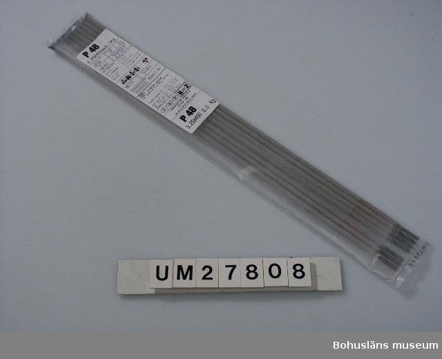 """Oöppnad plastförpacknng innehållande 7 svetselektroder, P 48.    Det fanns elektroder i många olika dimensioner, också längre elektroder. Dessa kunde vara 700 mm långa och räckte alltså längre, s k volymelektroder. De var avsedda för långa svetsfogar, exempelvis sammansvetsning av durk och vägg. Dessa långa elektroder satt  placerade på stativ. På så sätt kunde en man samtidigt serva 4-5 stativ och byta ut mot nya elektroder allt eftersom de tog slut.  Gubbarna  kallades skämtsamt """"robotar"""".  P 48:an såldes till Uddevallavarvet i tusentals ton. Givaren har under 30 år sålt dessa svetselektroder, bl a  till Uddevallavarvet och Mattsonföretagen i Uddevalla inom ett företag som heter Elga Skandinavien AB, """"quality and know-how in welding"""". Han har nu gått i pension men hade några gamla förpackningar kvar hemma."""