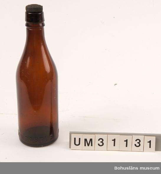 Bryggeriflaska, ca  60 cl., i brunt glas med gjutna refflor för skruvkork. Märkt i relief i glasmassan NERTILL på buken: WB REID & Co ltd NEWCASTLE  Svart bakelitkork med texten: THORNABY-ON TEES N E B Coy Thornaby ligger i North  Yorkshire, England  Funnen som vrakgods i Bohuslän.  Bernhardson beskriver barnens vrakletning i boken  Bohuslän - från Wämmer ock Kräppe  s. 128: Ätter e hale västa å massa lanfall brogga ongane sprenge langs strännena å röra i tanga - de leda ätter granne bôttlar mä konsti korkar å färger, de sanka på sånna. (Efter hård västanvind och högvatten brukade barnen springa längs stränderna och sparka i tången. Barnen sökte efter vackra buteljer med olikartade skruvkorkar och färger. Man samlade på sådana flaskor). Tidsbild 1920-talet  Litt: Bernhardson, C. G.: Bohuslän - från Wämmer ocH Kräppe. Uddevalla 1985.  För ytterligare upplysningar om förvärvet, se UM31100.