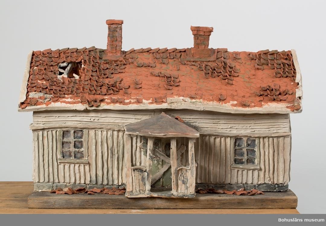 """Skulpturens titel: """"Övergivet hus i Bohuslän"""" Hus skulpterat i lera, bemålat med oxidglasyr och bränt i ugn. Förebilden är ett bohuslänskt dubbelhus  i förfallet skick. genom åren tillbyggt och ändrat. Detaljerna är noga redovisade."""