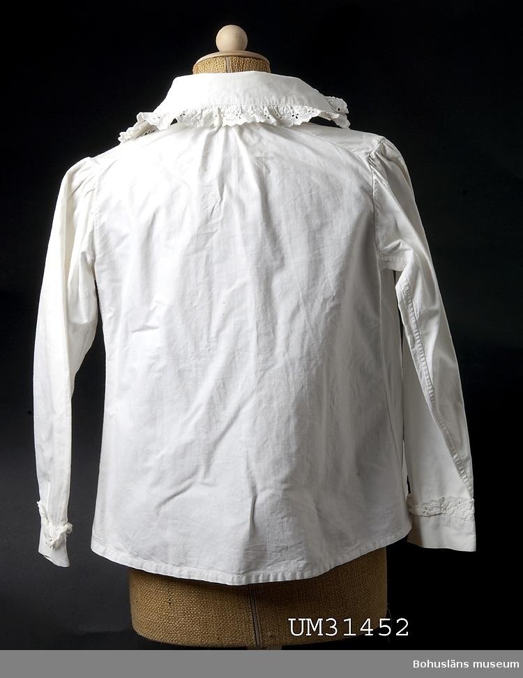 Enkel vidd nertill: 70 cm, Ärmlängd: 43 cm.  Långärmad blus av vit, kraftig bomull med knäppning fram. Hög krage med breda snibbar. Stråveck på framstyckena. Rynkad ärm. Längs krage, knappslå och ärmslut påsydd maskinväd vit bomullsbrodyr. Klädda vita knappar. Blusen är extra vid runt magen. Välsydd.  Blusen är tillverkad av Anna Olsson, född 1880, hemsömmerska, gift med Hilmer Olsson, fiskare f. 1874. Familjen bodde på Smögen. Anna och Hilmer hade fem barn. Anna sydde alla kläder till barnen och även till släkt och vänner. Anna hade en bror vars fru dog då deras fyra barn var 2, 4, 6 och 8 år gamla. Anna sydde alla kläder även till dem. Anna hade ingen formell yrkesutbildning men lärde dig av andra sömmerskor. Denna blus, samt en snarlik (UM31453) använde Anna efter det att barnen fötts hemma, vilket var det vanliga vid denna tid. Mödrarna låg ofta till sängs en tid efter förlossningen. Dessa blusar var tillverkade med extra omsorg för att man skulle se så fin ut som möjligt då man sängliggande tog emot besök av släkt och vänner. Ett vanligt samtalsämne mödrar emellan var de stickningar man kände i fötterna när det var dags att stå upp.  Anna och Hilmers barn föddes 1904 (Olle), 1906 (Ruth), 1908 (Henry), 1910 (Artur) och 1917 (Maria, gift Rödström).   Maria Rödström, gift med Karl-Olof Rödström, f. 1916 och son till Irene (1903 - 1995) och Evert Rödström, f. 1898.  Evert Rödström son till Sofia, f. 1872 och Frans Rödström, f. 1871. Evert bror till Gertrud Linnea Gunnarsson, f. 1896 med dottern Berit Gunnarsson, f. 1922. Se flera föremål från Smögen i samlingarna från denna familj.