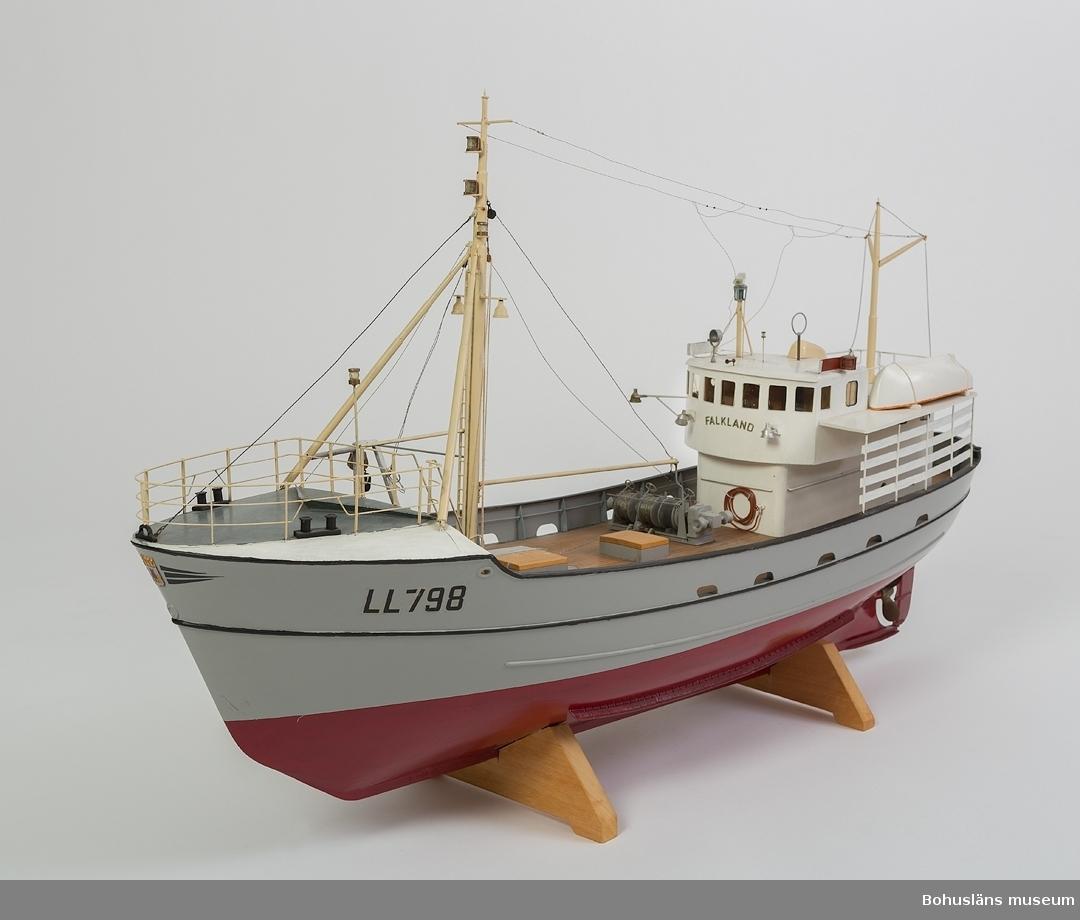 Modell av ståltrålaren FALKLAND. Modell av metallplåt, gråmålat skrov, vitmålad överbyggnad och rödmålad botten, trädäck och trålvinsch.  Märkt LL 798 och Falkland. Vid gåvotillfället stod modellen i en tillhörande glasad  mahognymonter.