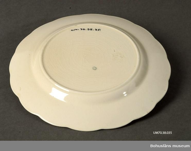 Ur lappkatalogen: Tallrik. Flat. Benfärgat porslin. Handmålad landskapsbild i botten. (Oljefärg). Diam. 24 cm. Funktion: Prydnad på vägg.