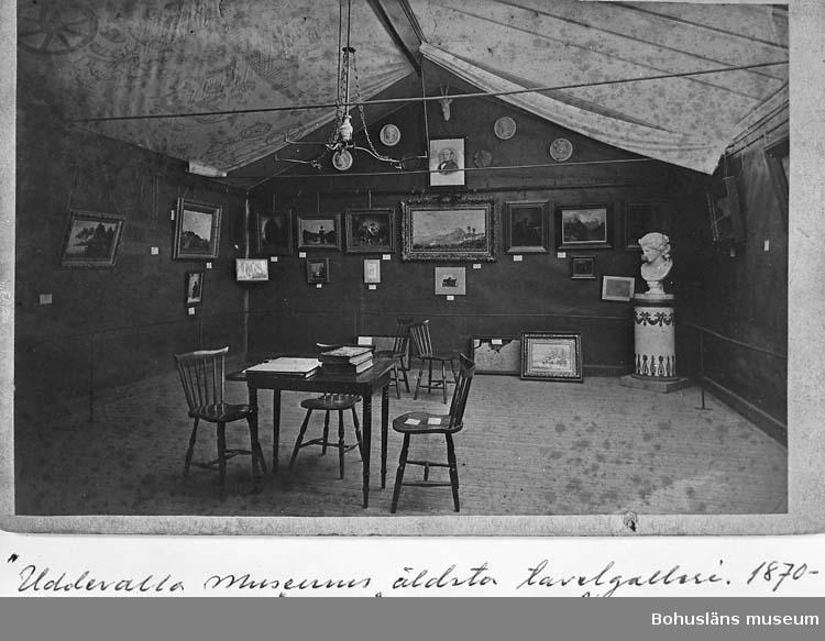 """""""Uddevalla museums äldsta tavelgalleri 1870-talets senare år, gåva av herr John Johnsson å Kristineberg vid Uddevalla 12/8 1918""""."""