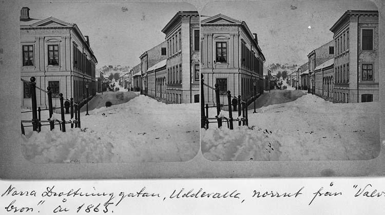 """Text på kortet: """"Norra Drottninggatan, Uddevalla, norrut från """"Valvbron"""", år 1865""""."""