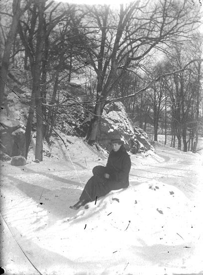 """Enl. text i blå bok: """"Dam sittande på sten i en park."""" ::"""