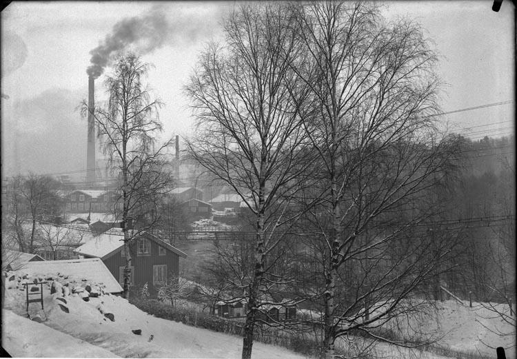 """Enligt fotografens anteckningar: """"Munkedals fabrik i bakgrunden. Sandbergs stuga i förgrunden."""""""