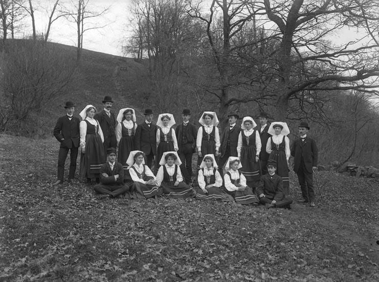 "Enligt fotografens noteringar: ""Folkdanslag i Munkedal omkr. 1910. Flera kända ........ V.L.A. Karlsson, Larsson, Schewenius?"""