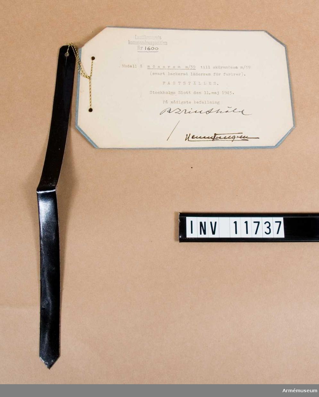 Grupp C I. Mössrem m/1939, t skärmmössa m/1939, svart lackerad läderrem för furirer. Fastställd 19430511. Modellexemplar. Gåva från Arméförvaltningens intendenturavdelning, modellkammaren.